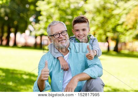 family, generation, gesture and people concept - happy grandfather and grandson showing thumbs up at summer park