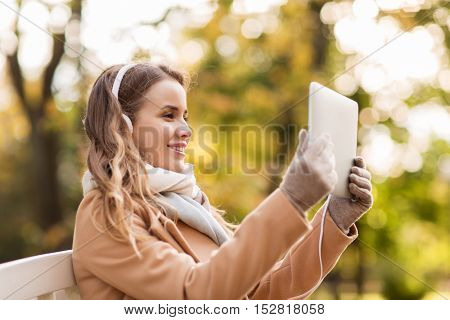 season, technology, communication and people concept - beautiful happy young woman with tablet pc computer and headphones listening to music or having video call and sitting on bench in autumn park