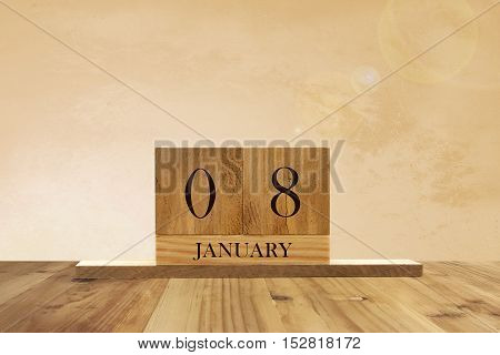 Cube shape calendar for January 08 on wooden surface with empty space for text.