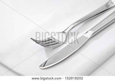 close up view of nice steel fork and knife on white napkin