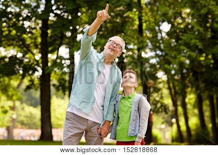 family, generation, communication and people concept - happy grandfather and grandson walking and pointing fingers up at summer park