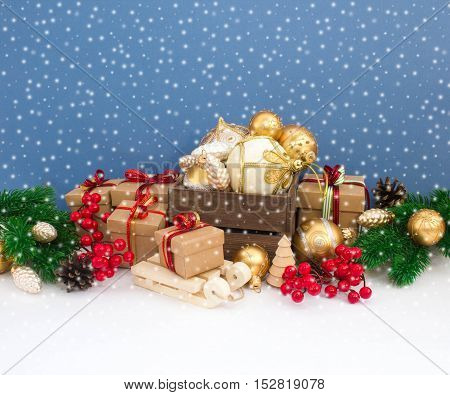 Christmas or New Year background: fur-tree, branches, gifts, colored glass balls, decoration and cones on a white, blue and snow background