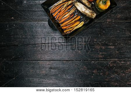 Yellow and green paprika, eggplants, tomato and carrots baked on metal baking tray