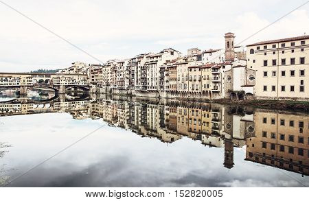 Ponte Vecchio and historical buildings are mirroring in the river Arno Florence Tuscany Italy. Travel destination. Beautiful place.