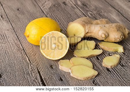 Lemon and ginger root on a gray wooden table.