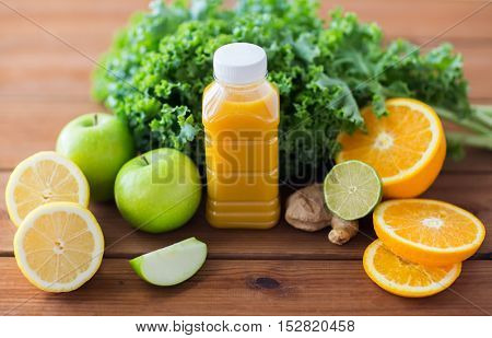 healthy eating, food, dieting and vegetarian concept - bottle with orange juice, fruits and vegetables on wooden table