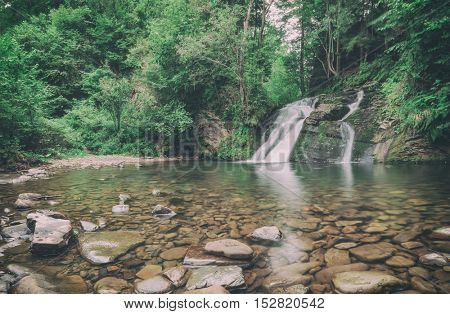 waterfall on mountain in summer time, toned like Instagram filter