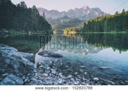 Fantastic sundown on mountain lake Eibsee, located in the Bavaria, Germany. Dramatic unusual scene. Alps, Europe, toned like Instagram filter