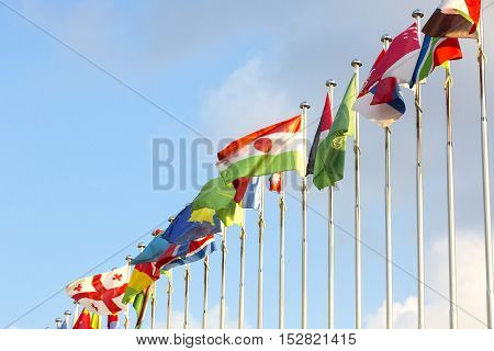 different countries flags on flagpoles on the sky background
