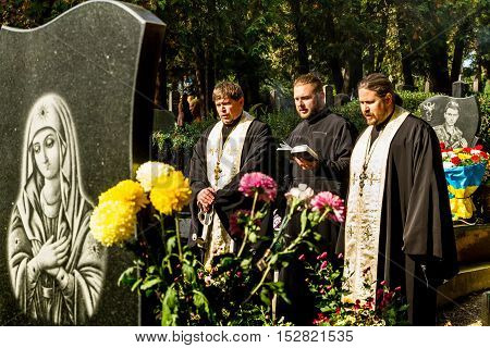 Uzhgorod Ukraine - October 14 2016: The priests pray at the graves of soldiers who died in the ATO zone during the celebration the Day of Defender of the Fatherland . This day Ukraine celebrates the Day of Defender of the Fatherland.