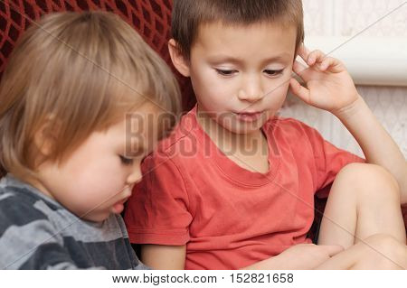 Two little kids sibling together looking book