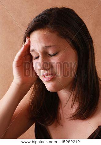 Infeliz adolescente com uma dor de cabeça.