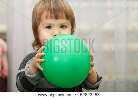 Little cute child puff out a ball