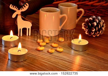 Small candles on the table small cookies. Two white cups of coffee. Christmas wooden moose figure decorative lump. Winter evening.
