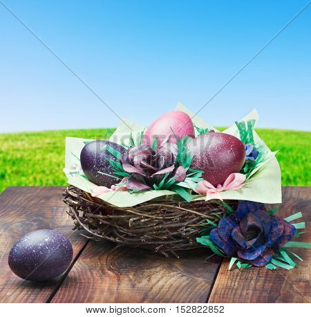 colorful painted Easter eggs in a basket on a background of nature