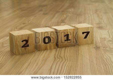 New Year 2017 written on wooden blocks on wooden background.