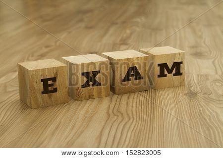 EXAM word written on wooden blocks on wooden background.