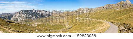 Panorama of the mountains in the national park of Montenegro and the narrow winding road leading up the mountain slope