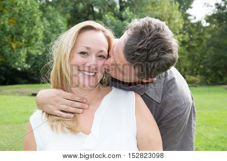 Happy Mature Couple In Love, Man Is Kissing His Wife .