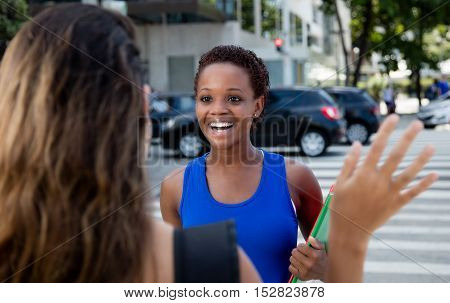 African american hipster girl meets a caucasian woman outdoor in the city in the summer