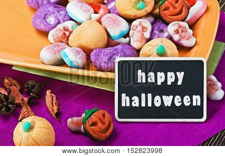 Halloween candy and blackboard for writing greetings