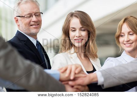 business, people and teamwork concept - smiling business people putting hands on top of each other in office