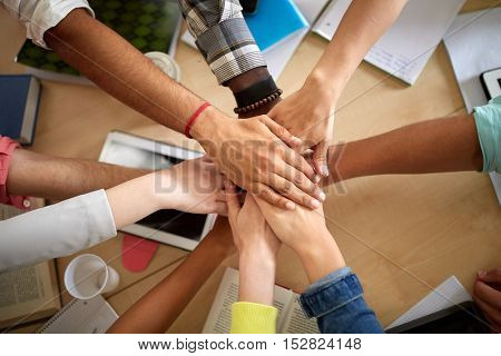 education, school, teamwork and people concept - group of international students with hands on top of each other over table