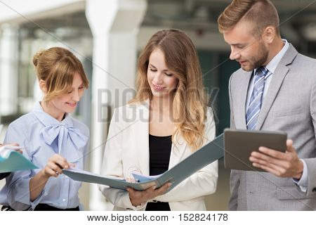 people, technology, work and corporate concept - business team with tablet pc computers and folders at office