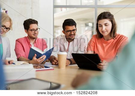 education, high school, people and technology concept - group of international students sitting at table with tablet pc computers, books and notebooks at university