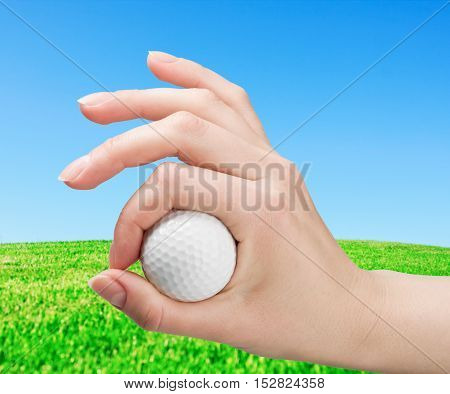 hand holds a ball for game in golf against a field