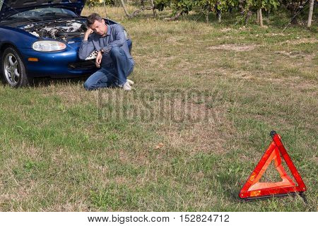 Triangle Warning Sign With Broken Down Car With Man