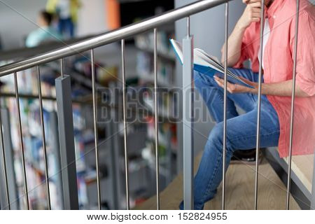 education, high school, university, learning and people concept - close up of student or young man reading book sitting on stairs at library
