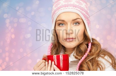 winter holidays, christmas, beverages and people concept - happy young woman in winter hat with red cup of tea over rose quartz and serenity lights background