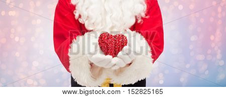 christmas, holidays, love, charity and people concept - close up of santa claus with heart shape decoration over rose quartz and serenity lights background