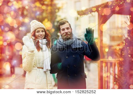 holidays, winter, christmas, gesture and people concept - happy couple of tourists in warm clothes waving hands in old town