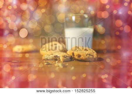 holidays, christmas, winter, food and drinks concept - close up of oatmeal close up of cookies and milk on wooden table over lights