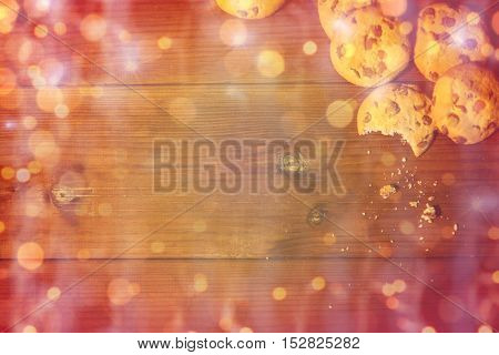 baking, cooking , christmas, holidays and food concept - close up of oat cookies on wooden table over lights