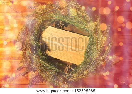 christmas, decoration, holidays and advertisement concept - close up of natural green fir branch wreath and wooden board over lights