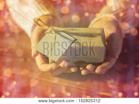 christmas, holidays, presents, new year and people concept - close up of woman hands holding gift box or parcel wrapped into brown mail paper with greeting card over lights