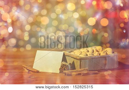 christmas, holidays, food and baking concept - close up of oat cookies in wooden box with blank greeting card and cinnamon on table over lights