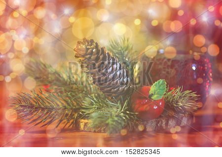 christmas, decoration, holidays and new year concept - close up of natural fir branch decoration and fir-cone and lantern on wooden table over lights