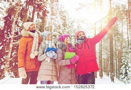 technology, season, friendship and people concept - group of smiling men and women with tablet pc computers pointing finger in winter forest