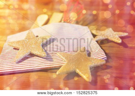 baking, cooking, christmas and holidays concept - close up of gingerbread cookies, kitchenware set and towel on wooden board at home kitchen over lights