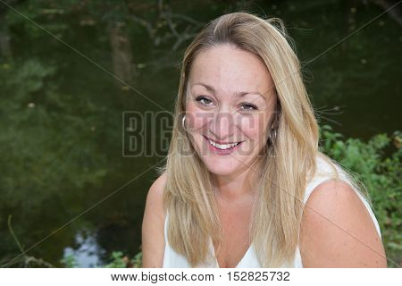 Young woman outdoors portrait with beautiful long hair smiles