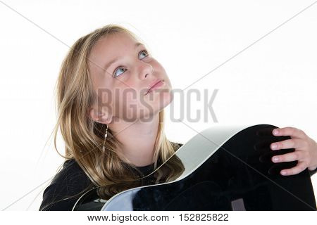Young girl pr child holding a guitar looking up