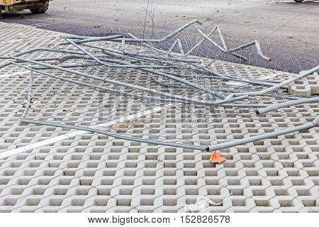 Crushed segments of safety mobile fence in pile on tiled ground.
