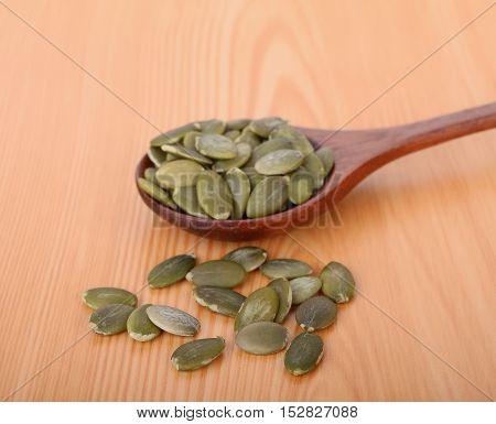 pumpkin seeds in wooden spoon on wood table
