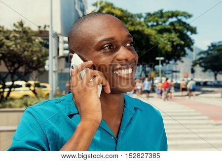 African american man using cellphone in the city in a warm cinema look