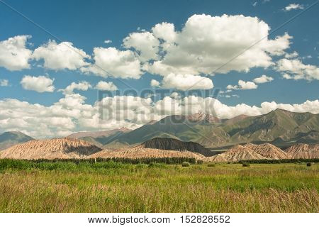 Magnificent view of the green valley at the Central Asian mountains covered with a cap of white clouds. Bright day in beautiful rural Kyrgyzstan country.