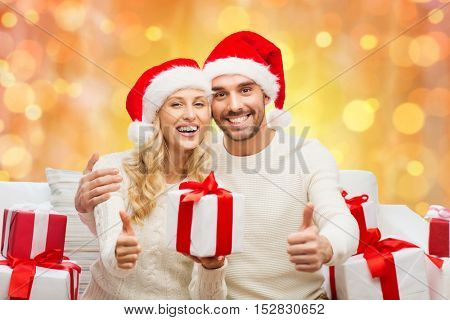 christmas, holidays and people concept - happy couple in santa hats with gift boxes sitting on sofa and showing thumbs up over holidays lights background